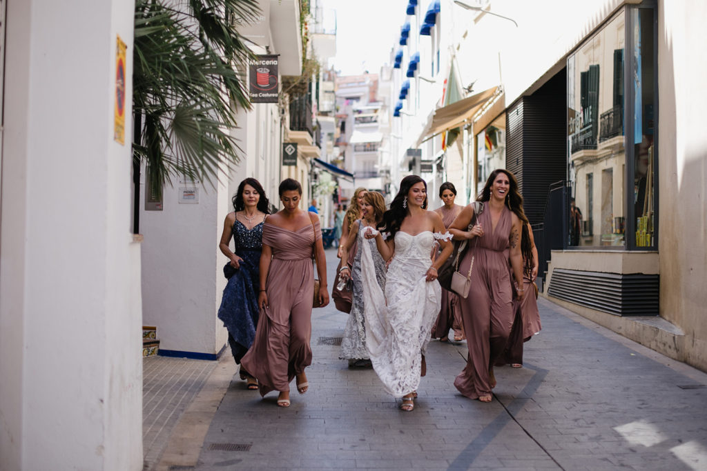 bride and bridesmaids walk down streets of sitges, spain, barcelona brides