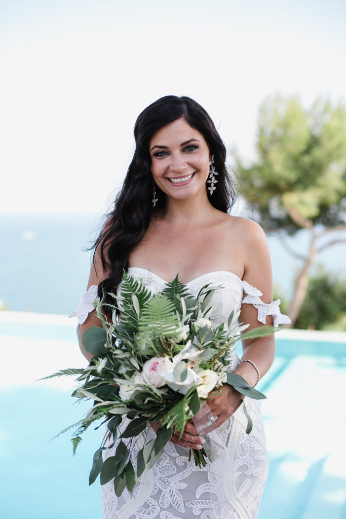 bride smiles and holds green and white bouquet near the pool at casa del mar, barcelona brides
