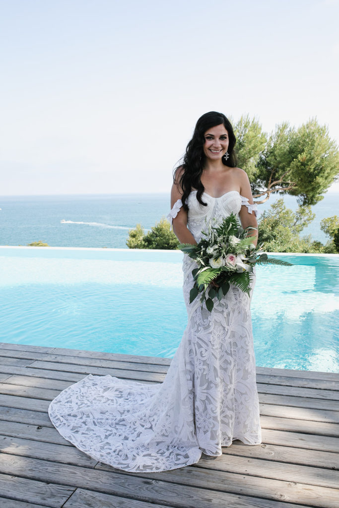 bride smiling and holding green and white bouquet in front of pool at casa del mar, sitges, spain, barcelona brides