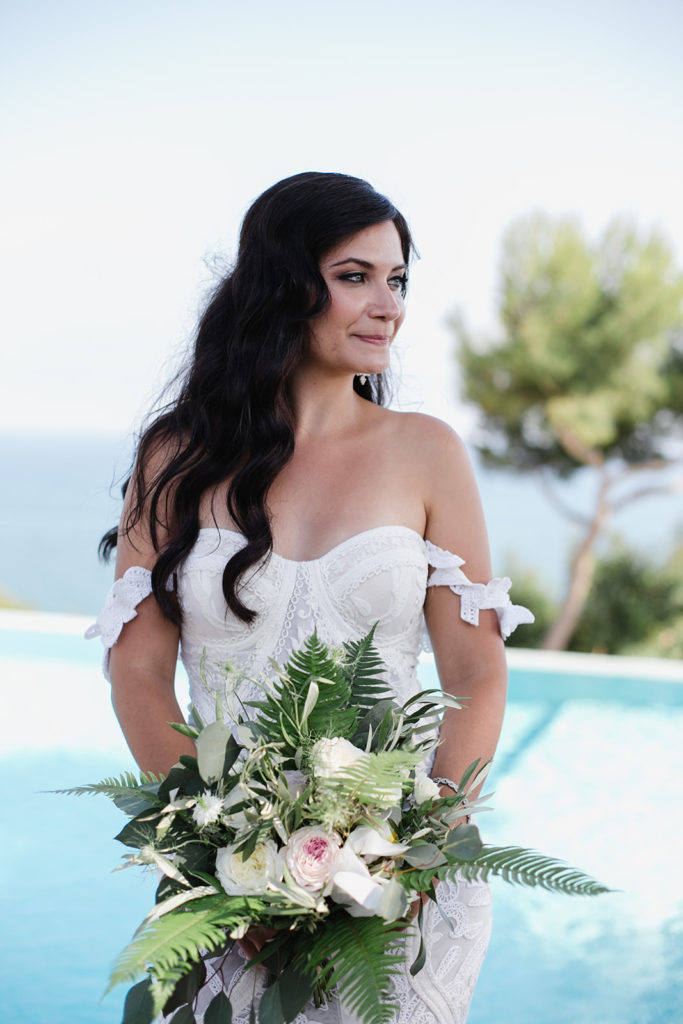 bride smiles and holds green and white bouquet in front of pool at casa del mar, barcelona brides