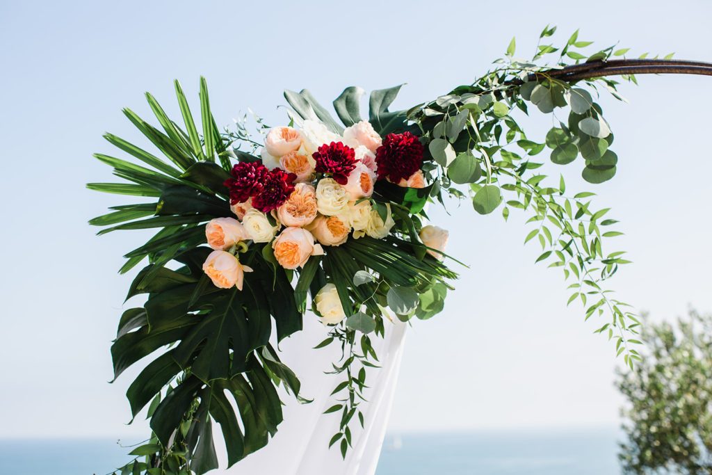red, pink, and white flowers with palm leaves on wedding arch at casa del mar, barcelona brides