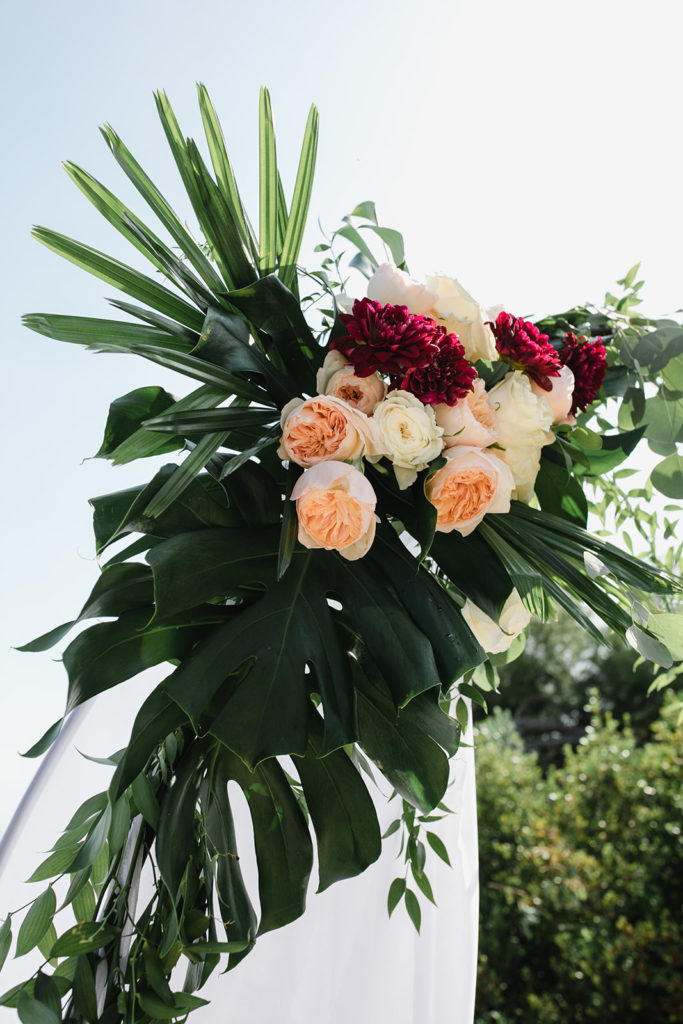 red, pink, and white flowers with palm leaves on corner of ceremony arch for wedding at casa del mar, barcelona brides