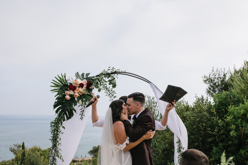 bride and groom kiss in front of wedding arch after ceremony, barcelona brides
