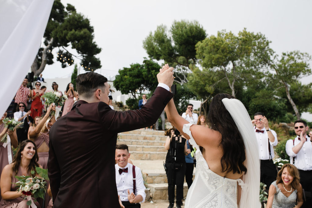bride and groom raise hands in front of guests after ceremony outside casa del mar, sitges, spain