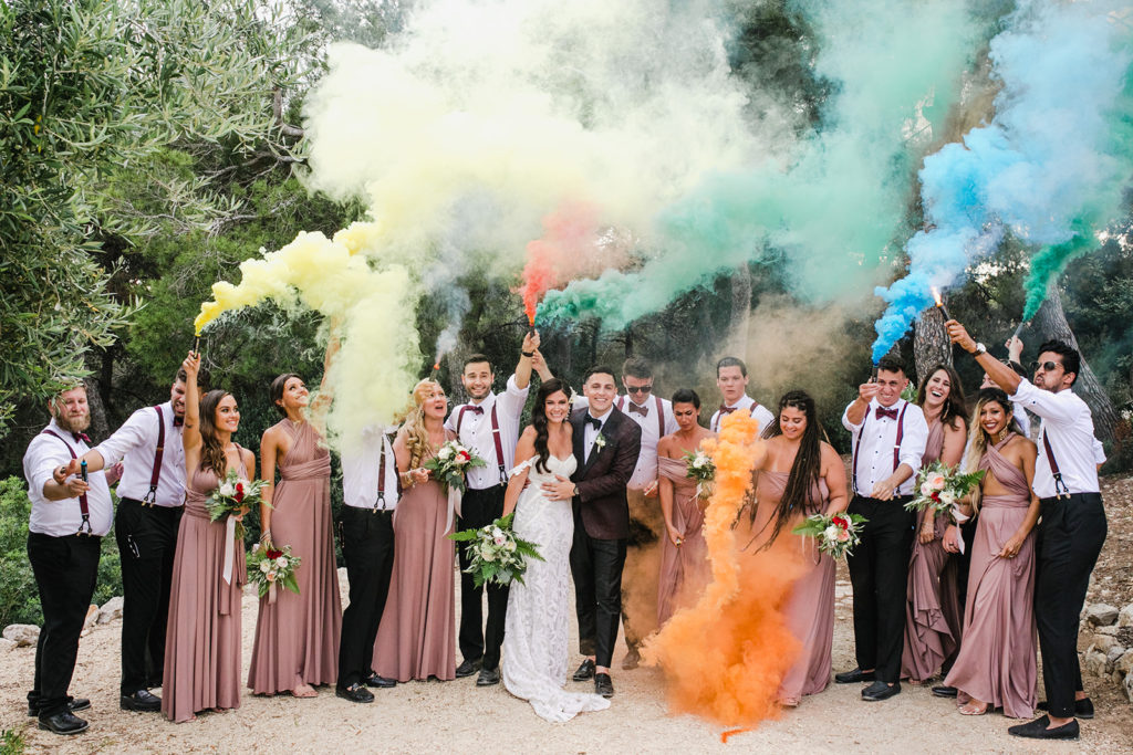 bride and groom with wedding party and colorful smoke bombs, casa del mar, barcelona brides