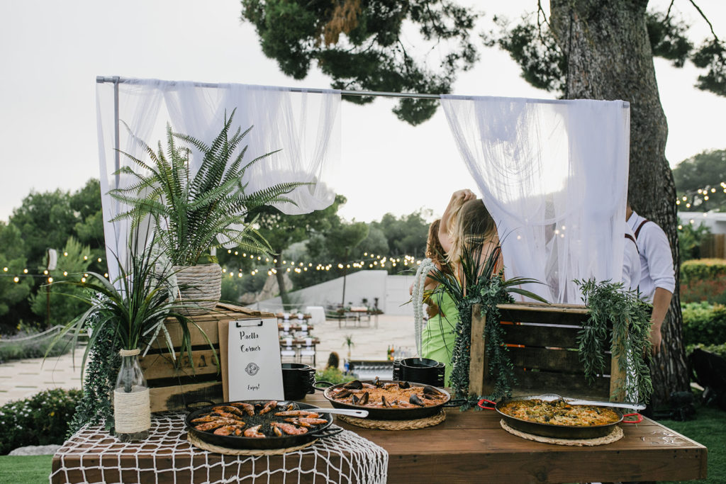 wedding buffet table with three paellas, wooden crates, and plants, barcelona brides, casa del mar