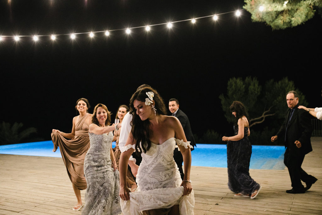 bride and guests dance in conga line by the pool, casa del mar, barcelona brides
