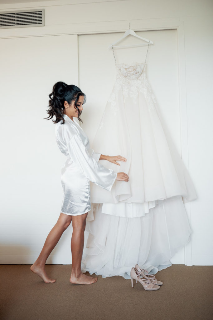 bride in white robe, admiring dress while getting ready, barcelona brides