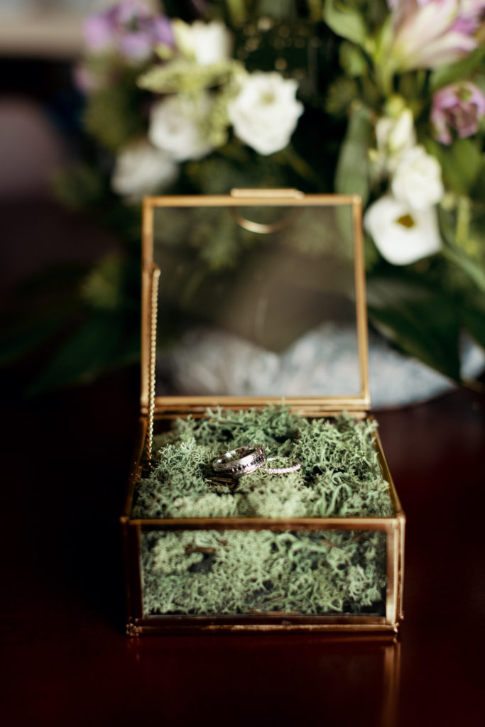 glass ring box filled with moss and rings on table with flowers, barcelona brides