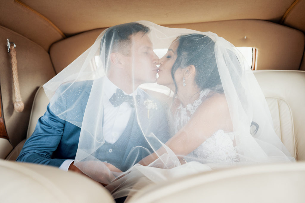 bride and groom kiss inside car with veil over them, sitges, spain, barcelona brides