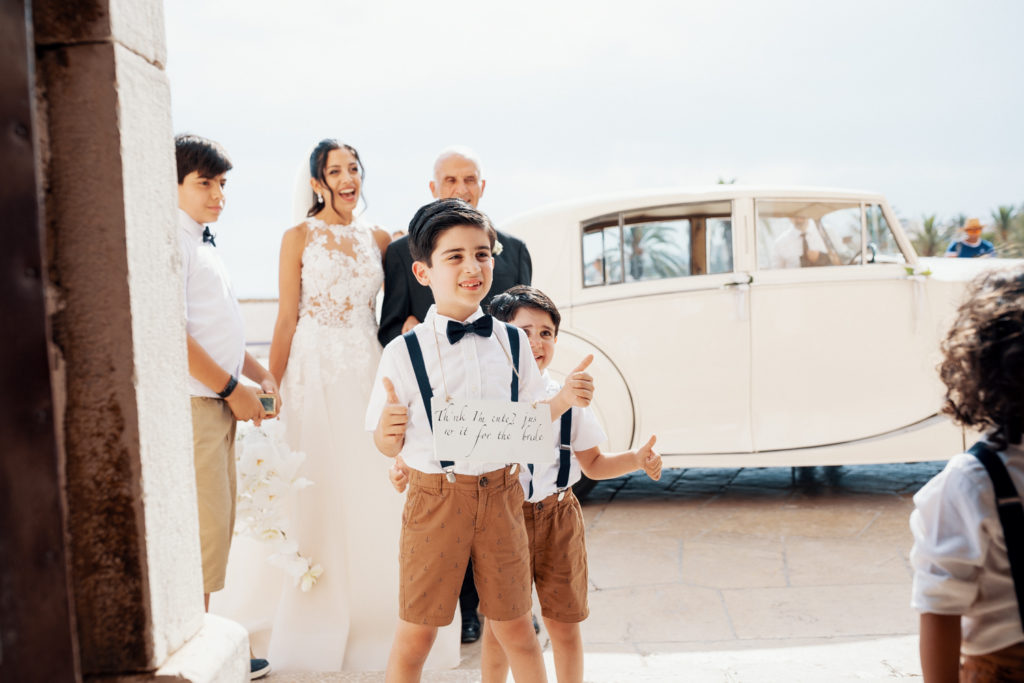 ring bearers and bride enter church in sitges spain, barcelona brides