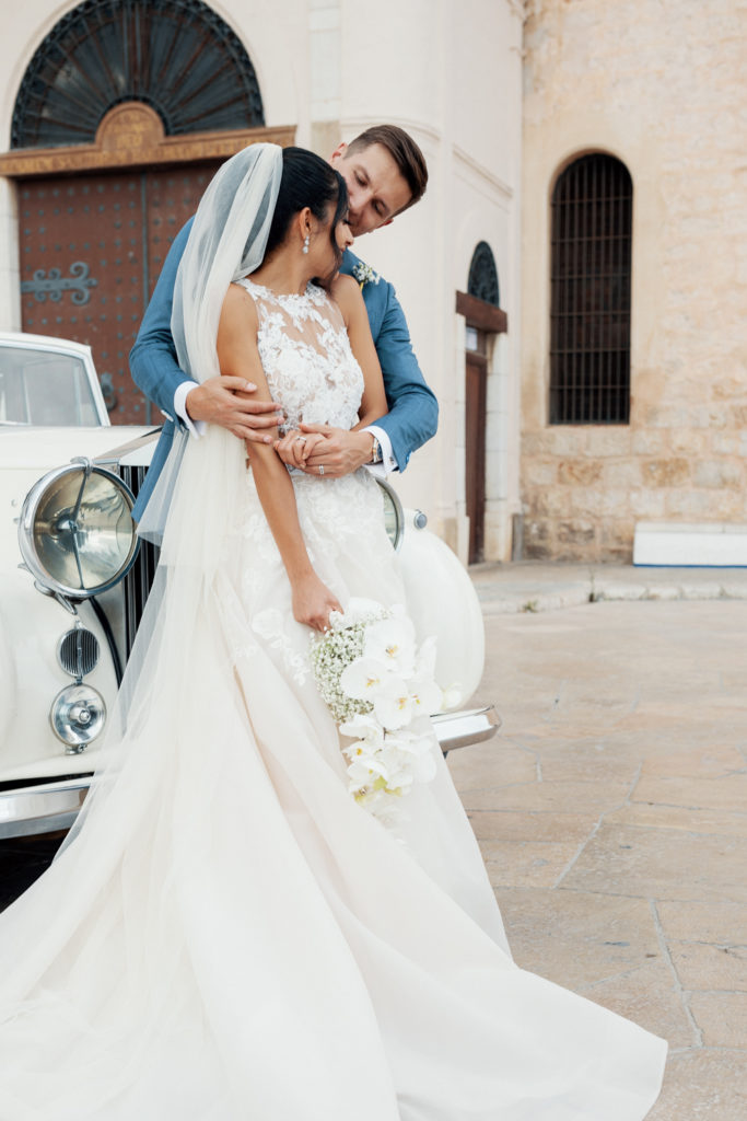 bride and groom embrace outside church of sitges, spain, barcelona brides