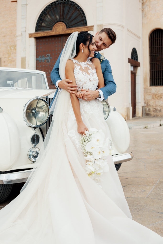 bride and groom embrace outside sitges church, spain