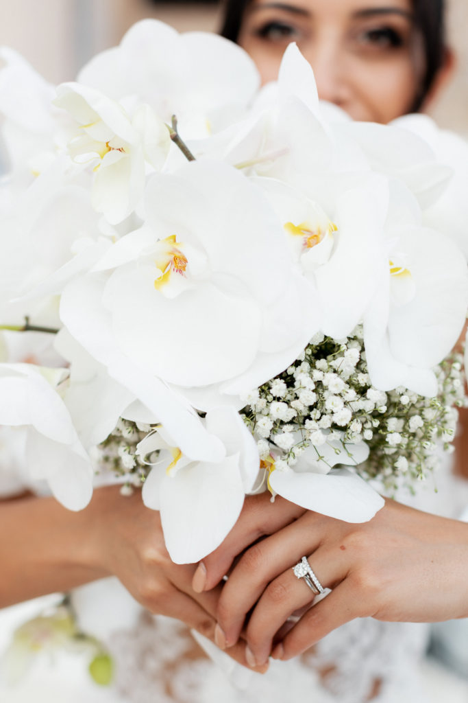 bride behind floral bouquet of white orchids and babys breath, barcelona brides