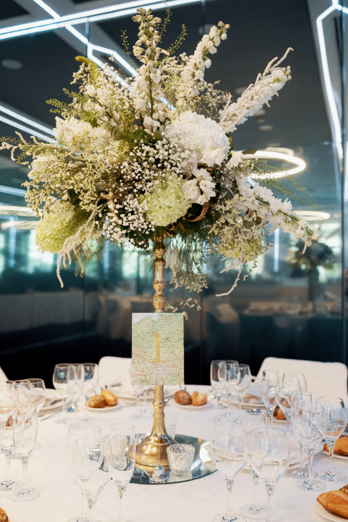 centerpiece of all white flowers and table number 1, barcelona brides