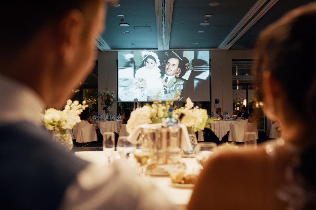 bride and groom watch slideshow at dinner, barcelona brides
