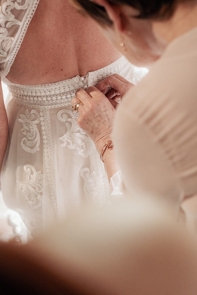 someone helps bride button dress before ceremony, barcelona brides, spain