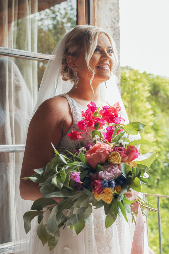 bride smiles with multi colored bouquet villa catalina, sitges, spain, barcelona brides