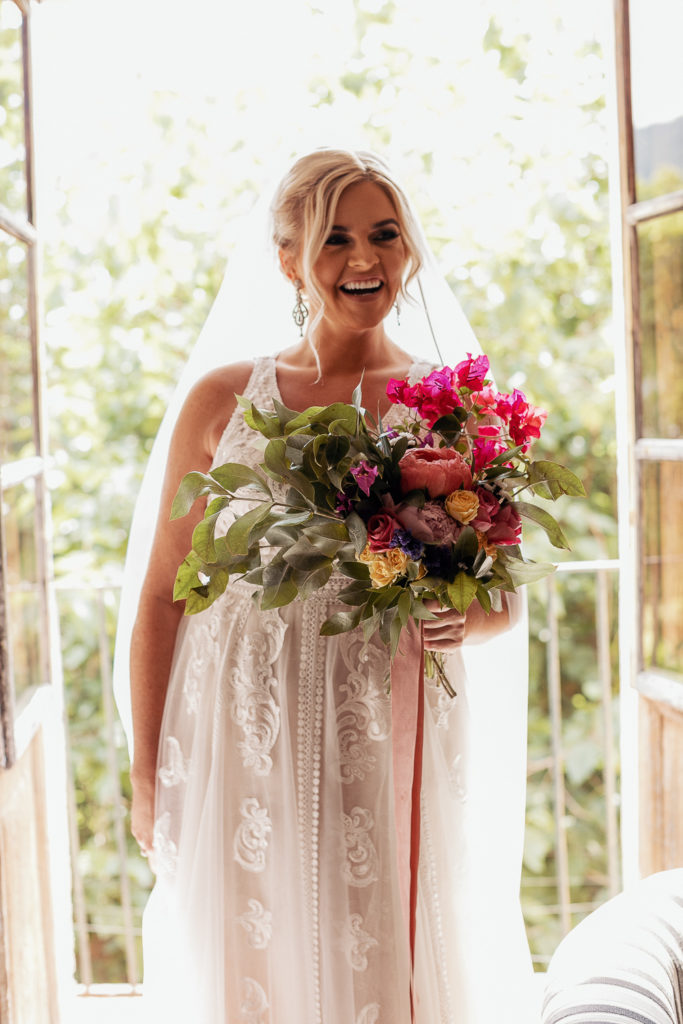 bride smiles with multi-colored floral bouquet in window of villa catalina, sitges spain, barcelona brides