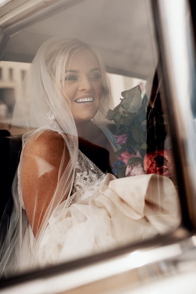 bride smiles in car on way to ceremony with bouquet, sitges, barcelona brides, spain