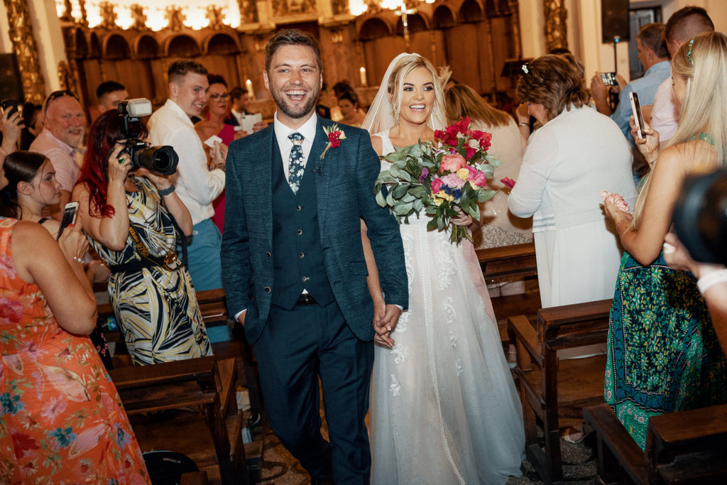 bride and groom smiling walking down aisle of church, sitges, spain, barcelona brides