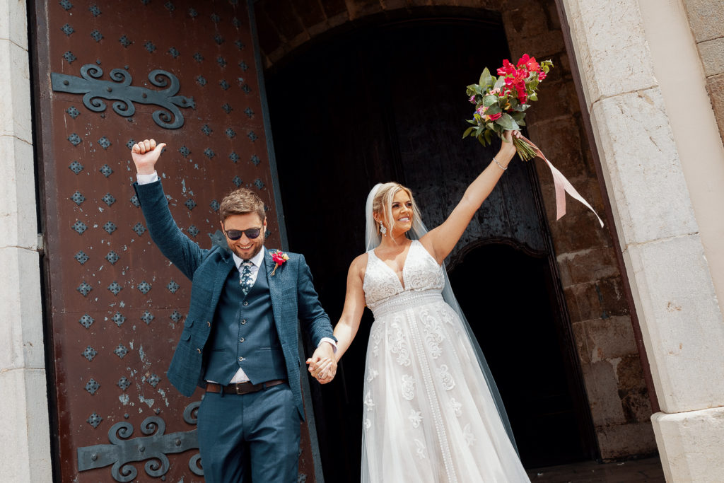 bride and groom with arms in the air outside church, sitges, spain