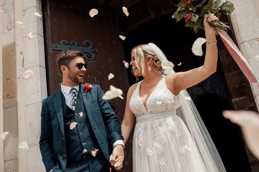 bride and groom smile outside church with flower petals in the air, sitges, spain, barcelona brides