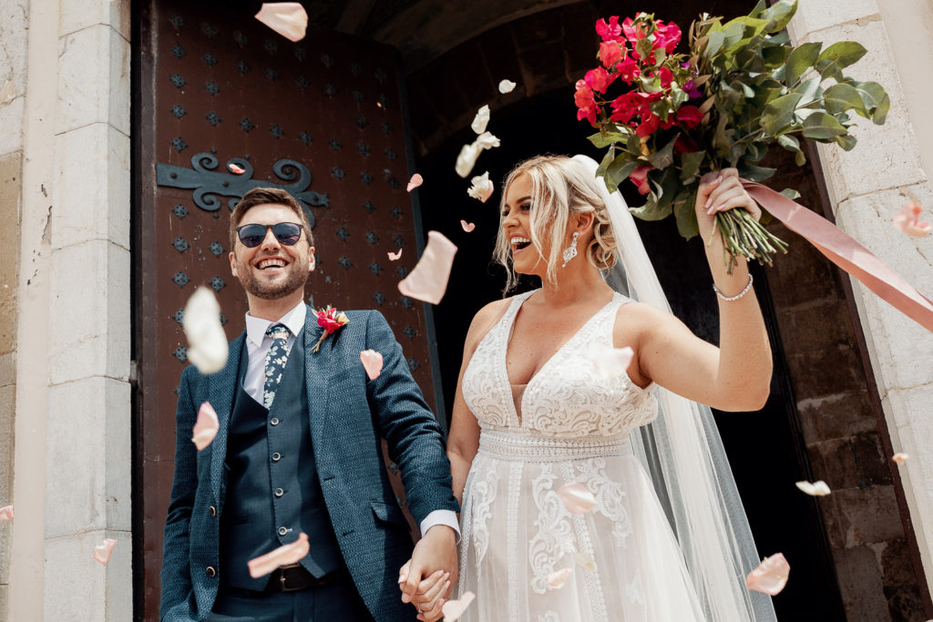 bride and groom smile outside church with flower petals, barcelona brides, spain