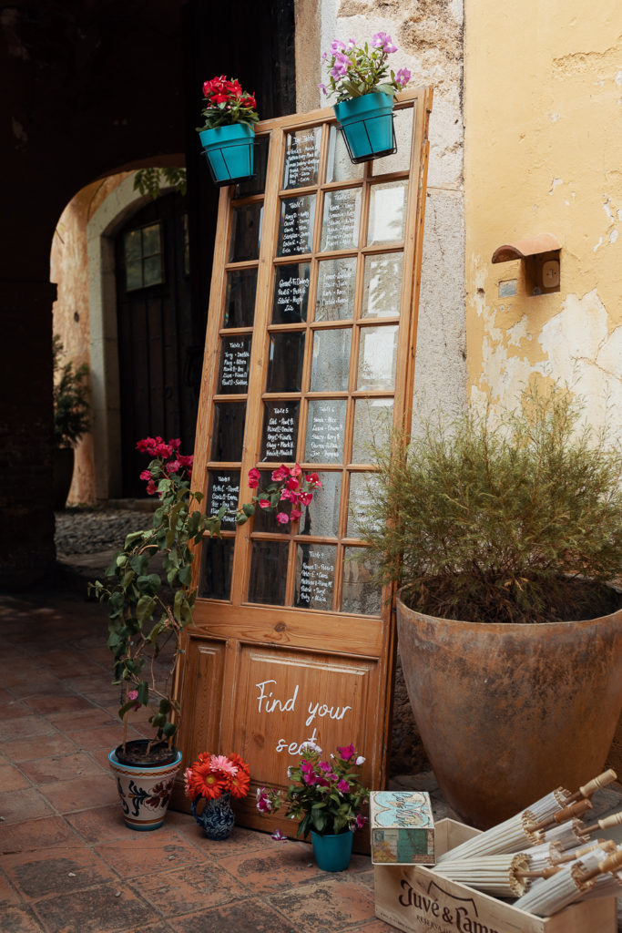 wedding table assignments written on paneled glass door with potted plants, barcelona brides