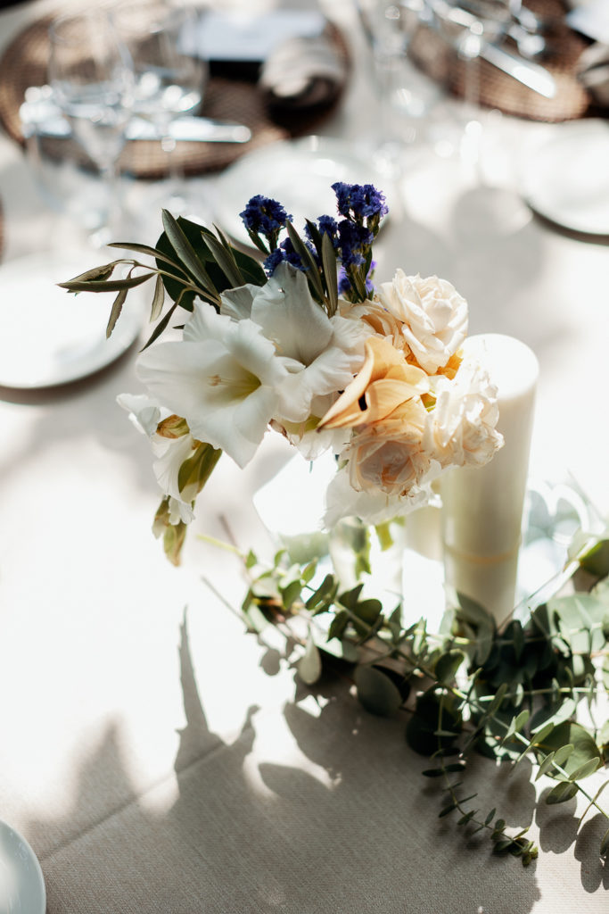 wedding table setting with clear bud vase filled with greenery, and white and yellow flowers, barcelona brides, spain