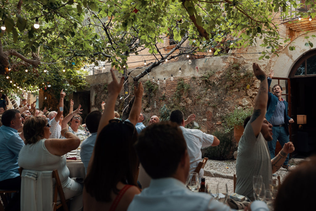 guests cheer during speeches in garden of villa catalina, sitges, spain, barcelona brides