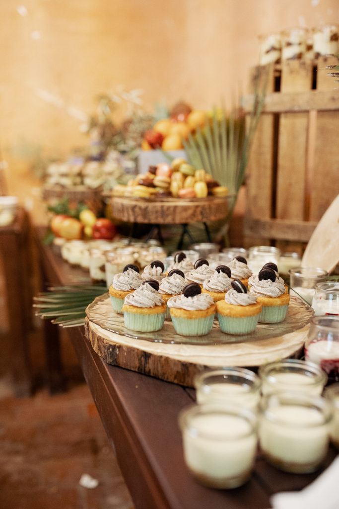 wedding buffet table covered in oreo cupcakes, puddings, wood, and palm leaves