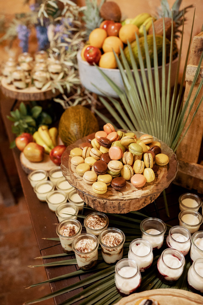 dessert table with palm leaves, french macarons, puddings, and fruit, barcelona brides, spain