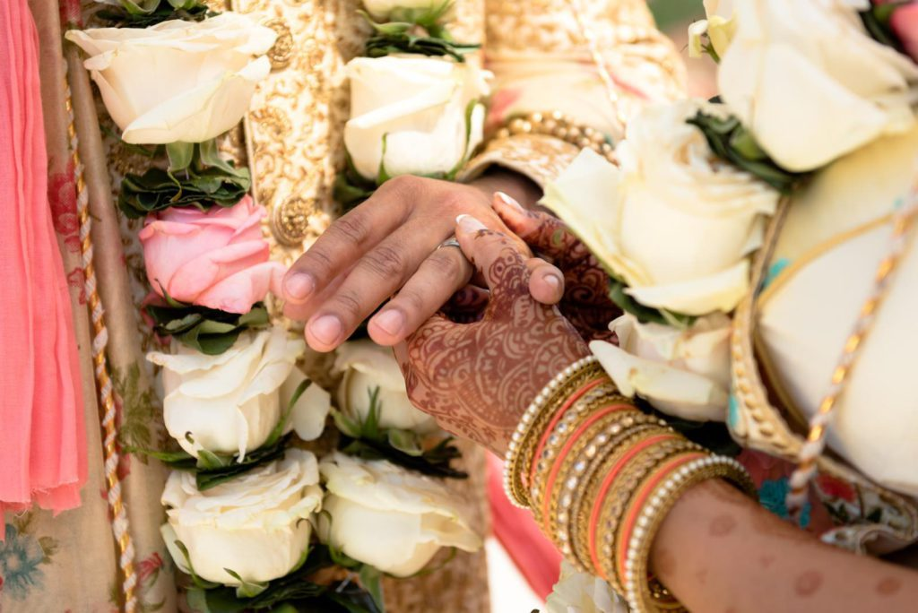 Bride and groom holding hands. Bride is showing henna on hand. Planning an Indian Wedding