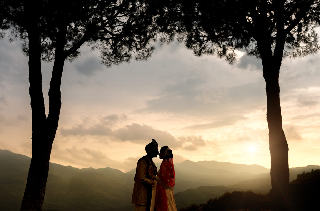 Hindi bride and groom silhouetted by sunset