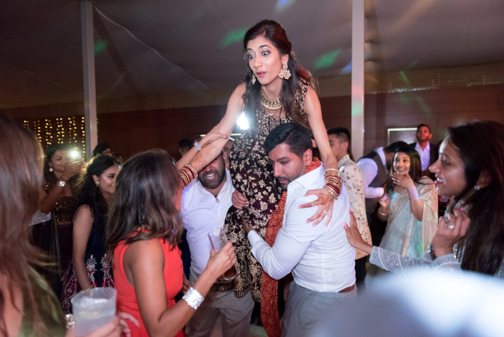 bride gets lifted into air by wedding guests