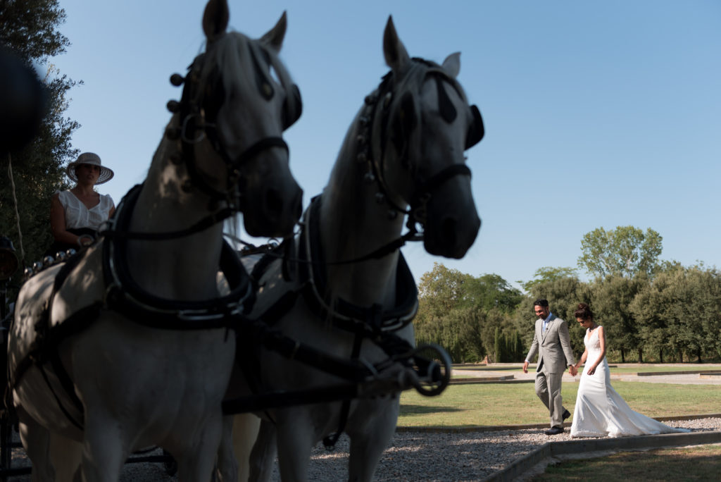 Bride and groom walk toward horse and carriage