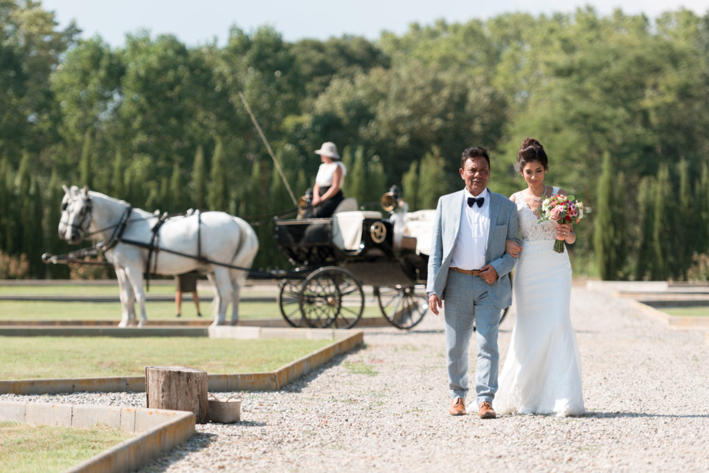bride walks with her father and horse and carriage in the background