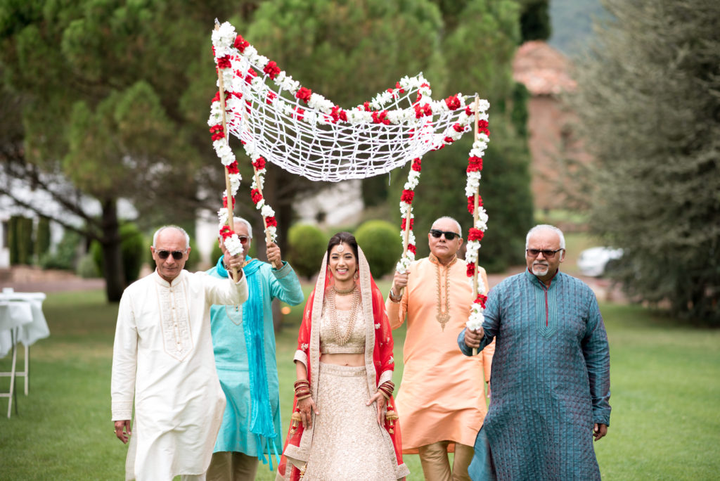Hindu bride walking with family carrying a floral canopy above her head