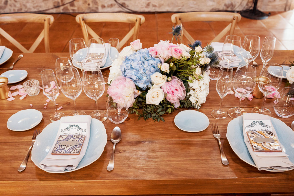 wedding place settings with wood table, blue plates, pink and blue flowers, and menu decorated by Barcelona Brides