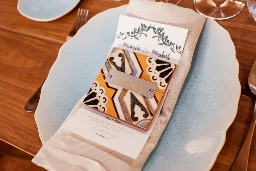 wedding place setting with blue plate, linen napkin, Spanish tile design, and menu card, Barcelona Brides