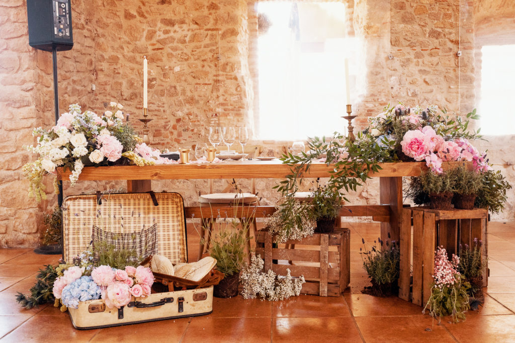 wedding decor table covered in pink florals with wooden crate accents and an old fashioned suitcase, Barcelona Brides