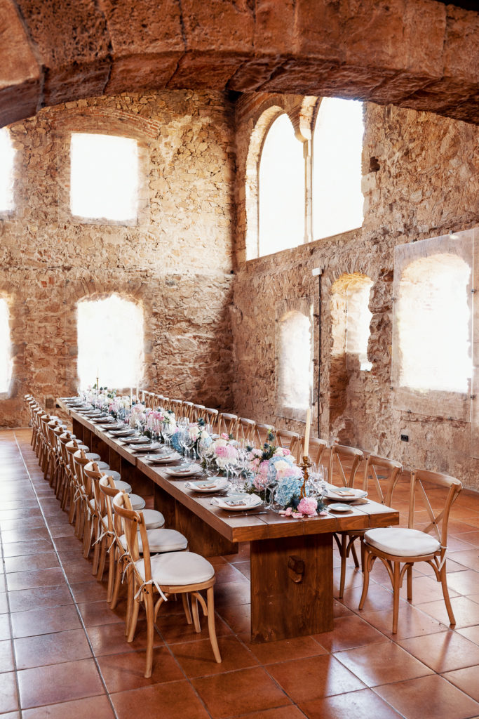 wedding table with place settings, blue and pink florals, and candles at convent Blanes, Spain, Barcelona Brides