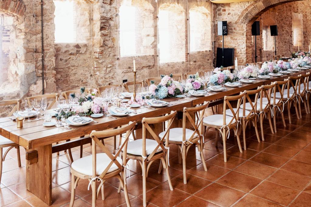 wedding dining table with blue and pink flowers, candles, place settings in convent of Blanes, Spain