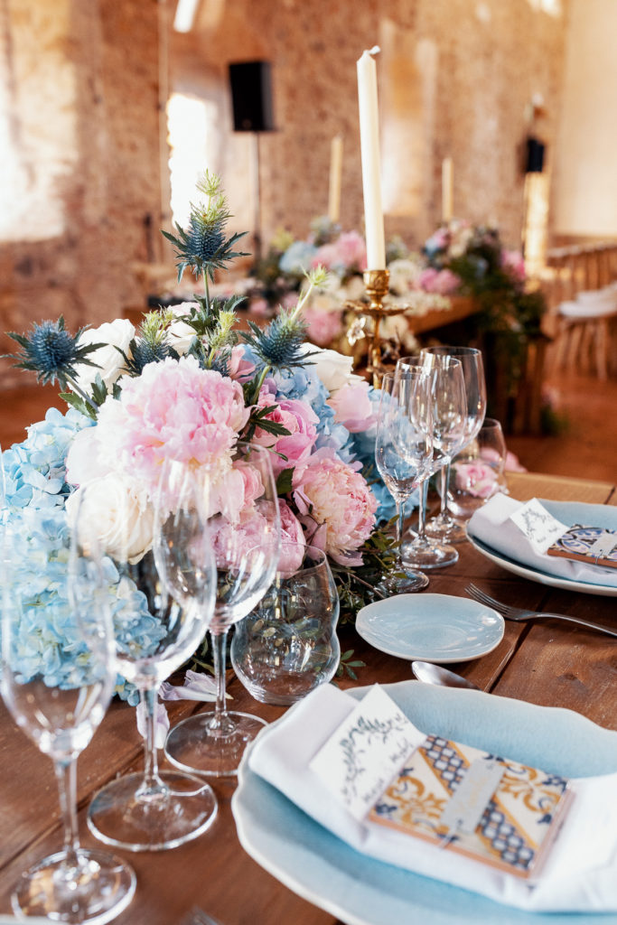 wedding tablescape with blue and pink florals, wine glasses, place settings, and candles, Barcelona Brides