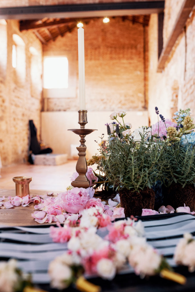 pink flower petals, rosemary, brass candlestick and candle, convent in Blanes, Spain