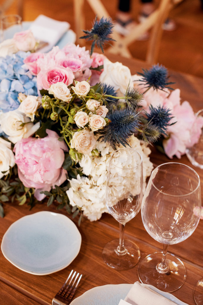 wedding centerpiece with blue and pink flowers, glassware, and blue plates, Barcelona Brides