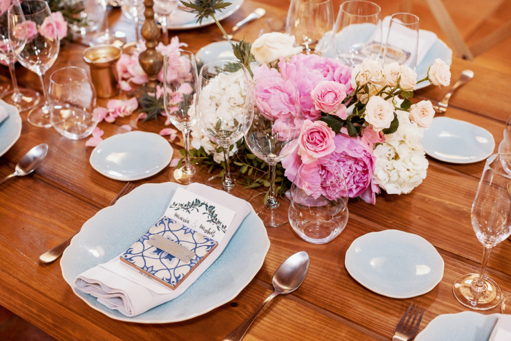 wedding table scape with pink and white flowers, glassware, blue plates with linen napkins, spanish tile, and name tags, Barcelona Brides