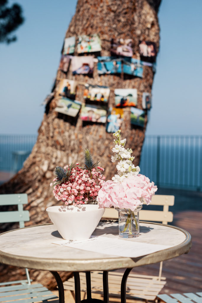 wedding guest sign in on table with pink flowers outside convent in Blanes, Spain