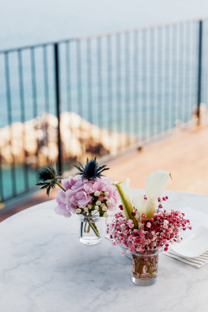 wedding cocktail table with centerpieces of pink flowers and white lilies, Blanes, Spain